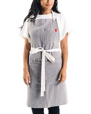 Photo of a woman in a chef inspired apron against a white background.