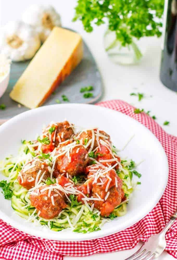 Photo of a white plate full of meatballs over a bed of zucchini noodles.
