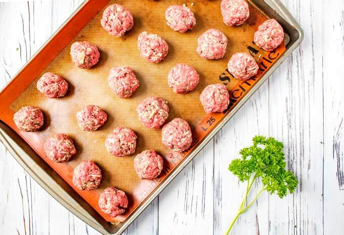 Baking sheet of meatballs made out on a lined baking sheet.
