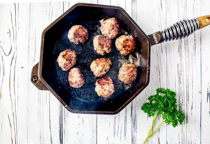 Meatballs being browned in a cast iron skillet.