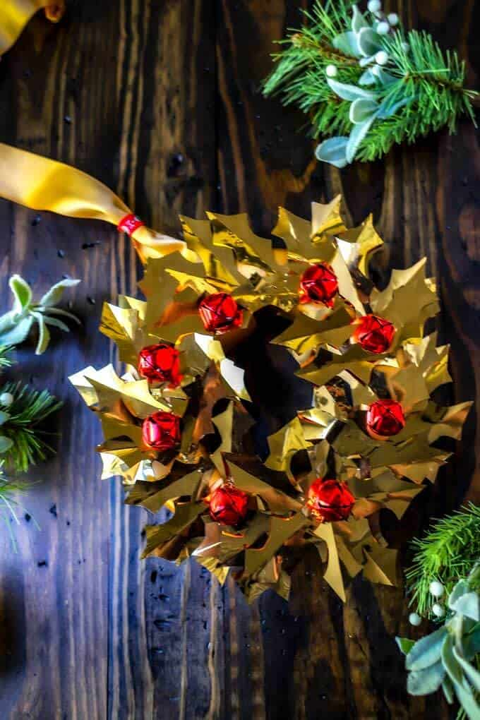 Photo of gold DIY Christmas Wreath on a dark background with greenery around it