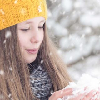 Photo of a tween girl in the snow with a yellow had and a handful of snow.