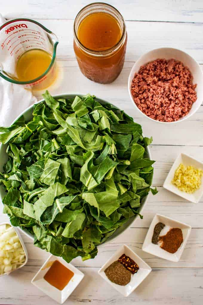 The ingredients for Slow Cooker Collard Greens measured out in prep bowls against a white background.