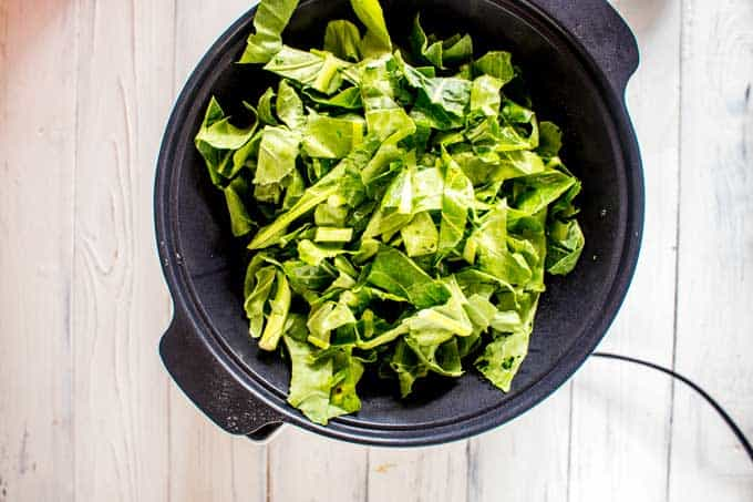 Photo of collard greens being added to a slow cooker sitting on a white background.