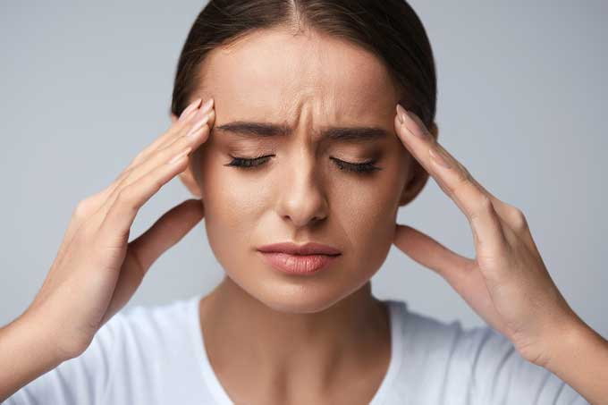 Photo of a women with a tension headache clutching both sides of her head.