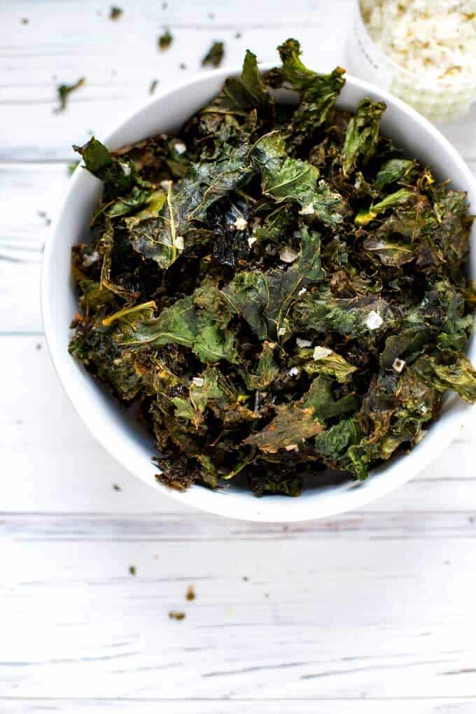 Photo of homemade kale chips in a white bowl against a white wooden background with crumbled kale chips scattered.