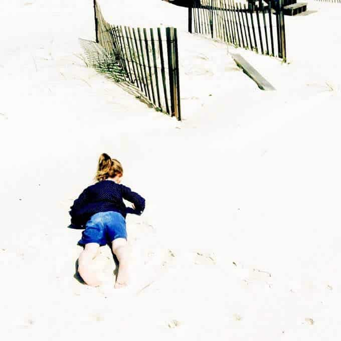 Toddler girl face down in the sand