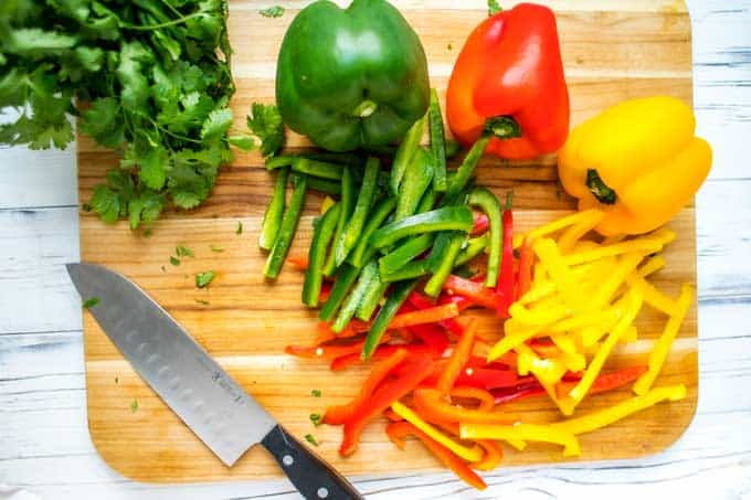 A red pepper, green pepper and yellow pepper cut up to make Sheet Pan Fajitas