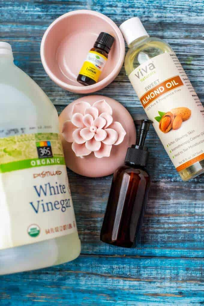 Ingredients for DIY Furniture Polish - Vinegar, Lemon Essential Oil, Almond Oil and Amber Bottle.