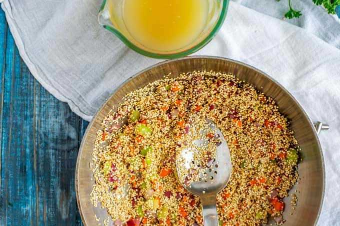 Photo of quinoa being toasted in a pot with a spoon in it and broth sitting nearby.