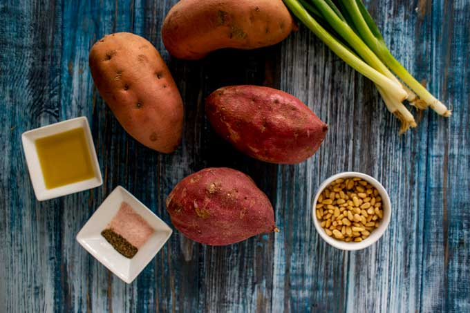 Photo of sweet potatoes, green onions, olive oil, pine nuts, and seasonings against a blue background.