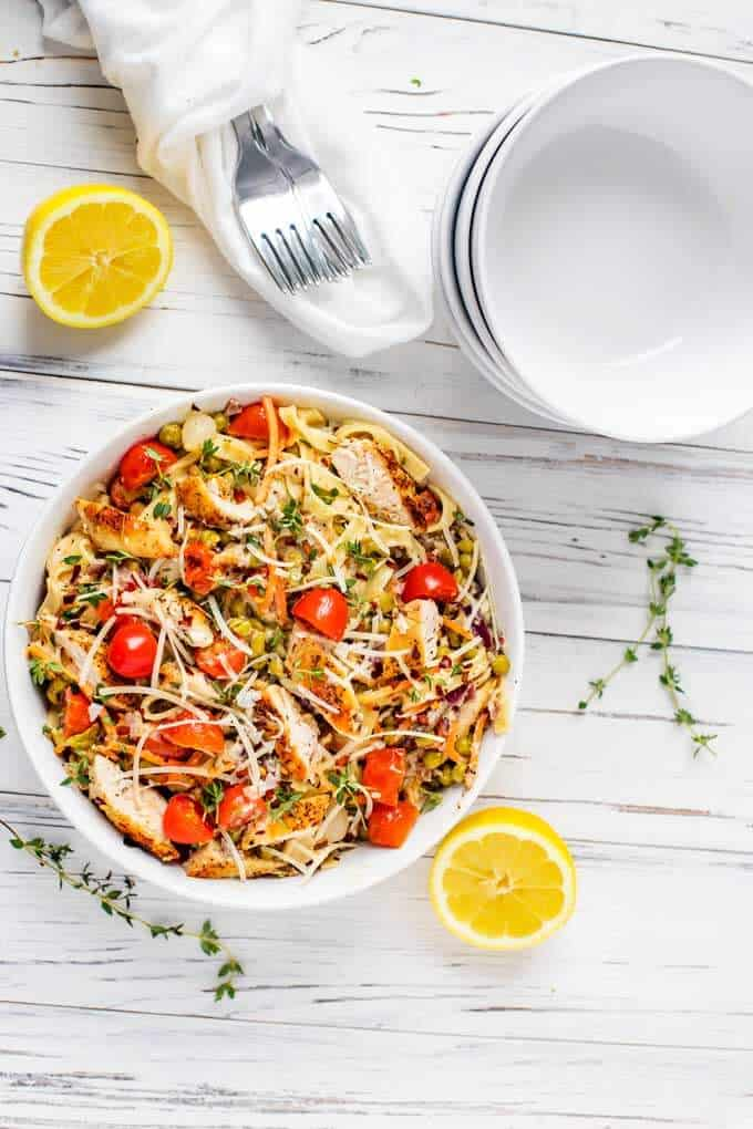 Overhead photo of Pasta Primavera with Chicken in a large white bowl with serving bowls behind it.