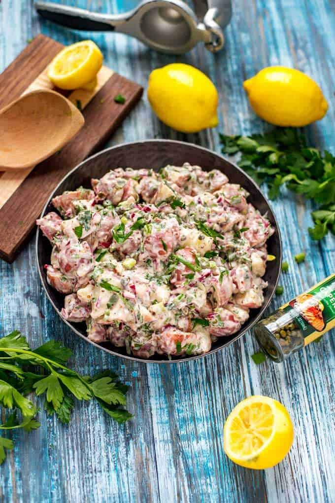¾ overhead photo of Red Skin Potato Salad with Capers on a dark background.