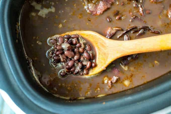 Photo of a wooden spoon lifting out a spoonful of cooked black beans from a slow cooker.
