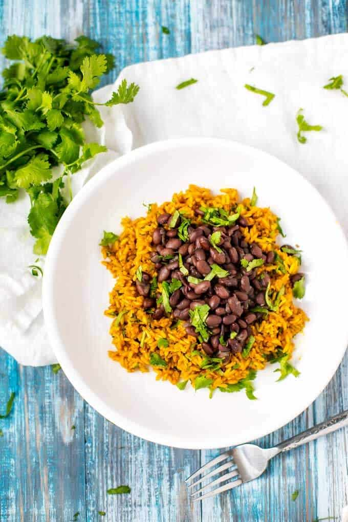Photo of Slow Cooker Black Beans on a bed of turmeric rice on a white plate against a weathered blue background.  A bunch of parsley is above the plate with cut parsley spread around.