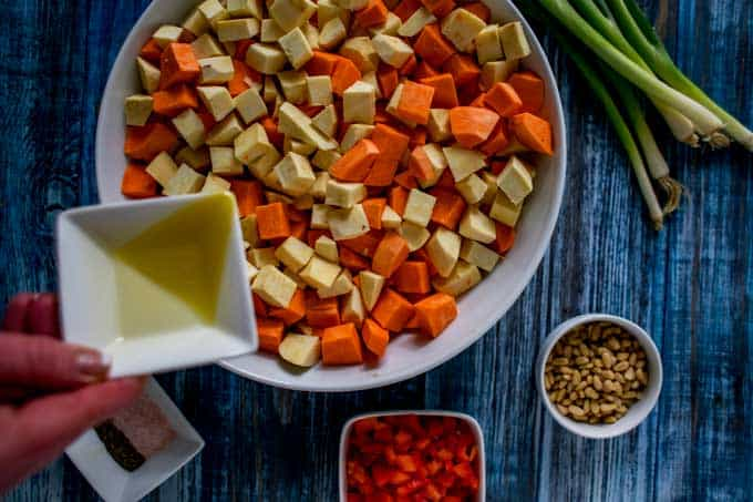 Photo of the first process photo for a roasted sweet potato salad. Cube sweet potato in a large white bowl are being drizzled with oil.