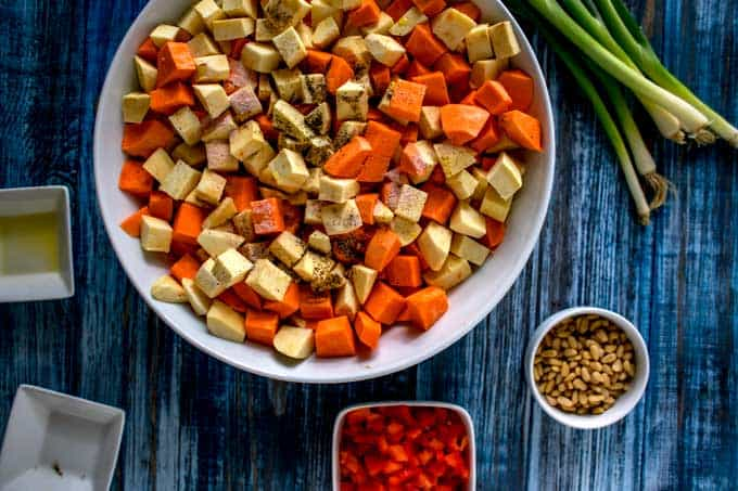 Second process photo for roasted sweet potato salad: seasonings are being added to cubed sweet potatoes and oil.