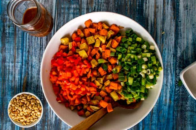 Sweet potatoes, chopped scallions, and chopped red pepper in a large white bowl.