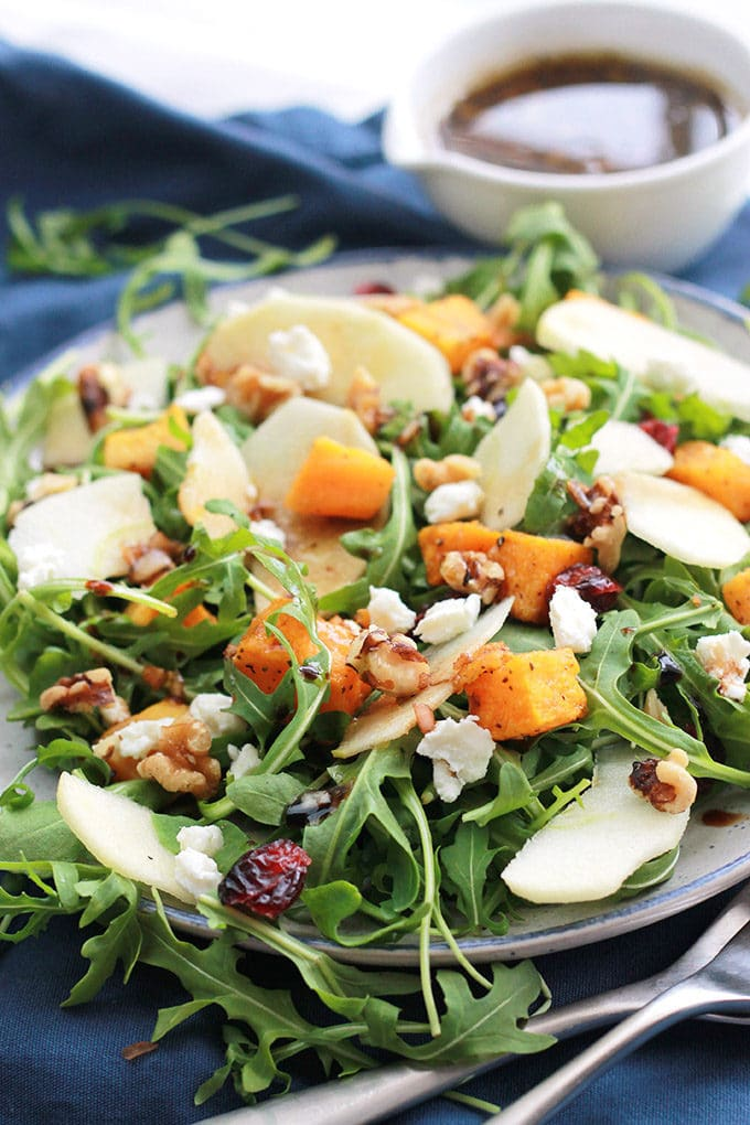 Close-up of Butternut Apple Arugula Salad with Balsamic Dressingloaded with tender roasted butternut, crisp sliced apple, spicy arugula, sprinkled with dried cranberries, walnuts, and creamy goat cheese.