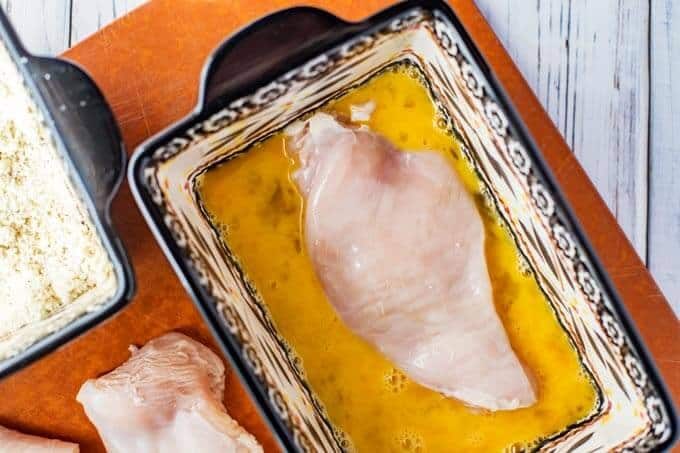 Process photo of air fryer boneless chicken breast being dipped in egg.