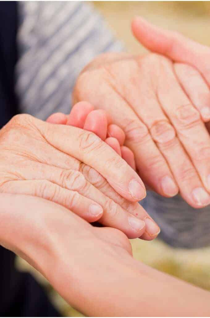 Photo of younger hands holding older hands.