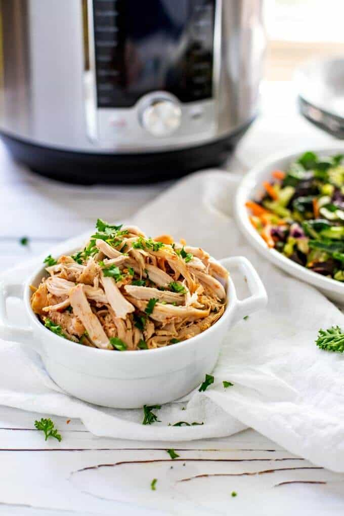 Photo of Instant Pot Shredded Chicken in a white dish and garnished with parsley taken from the side.