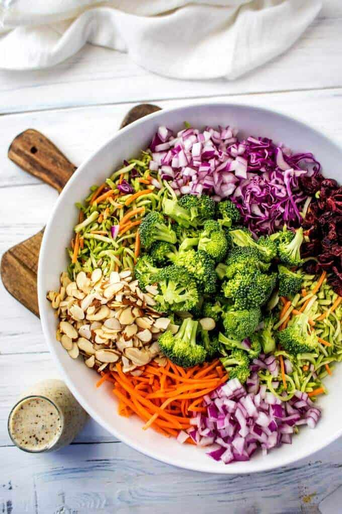 Photo of Broccoli Slaw Salad ingredients arranged in a large white bowl sitting on a cutting board.
