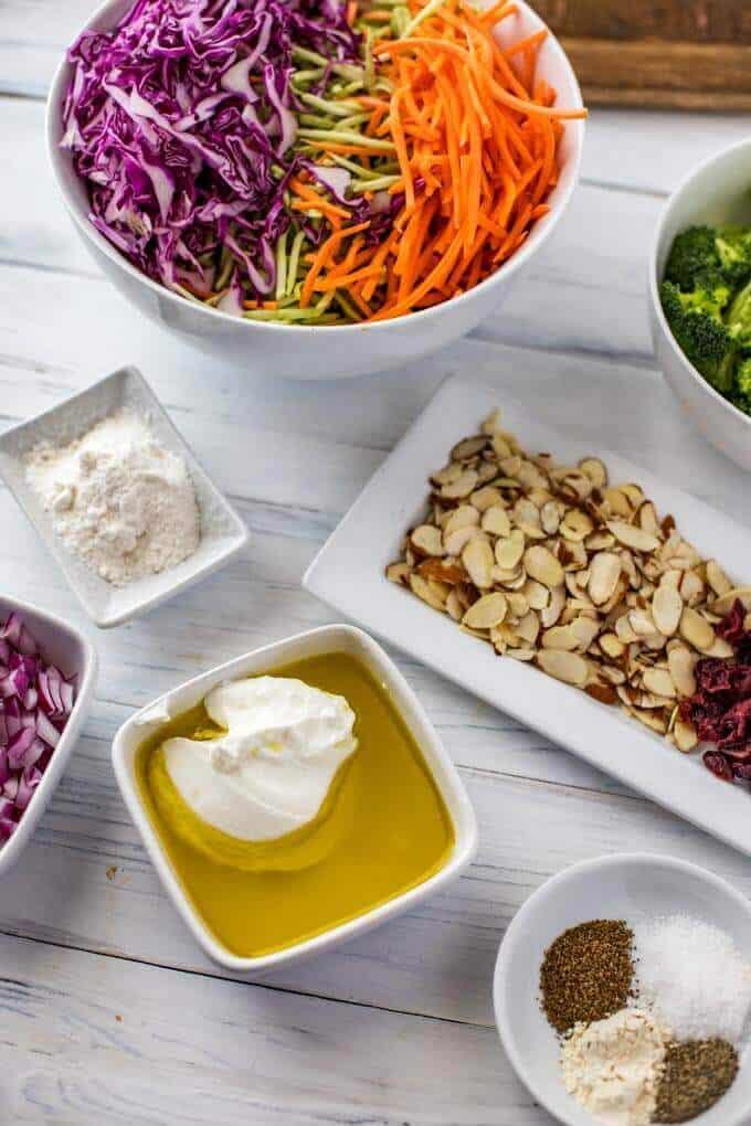 Photo of the ingredients for broccoli slaw salad: Greek yogurt, olive oil, lemon juice, Swerve, garlic powder, celery seed, cayenne pepper, salt, and pepper, broccoli, broccoli slaw, red onion, almonds, carrots, cabbage, cranberries.