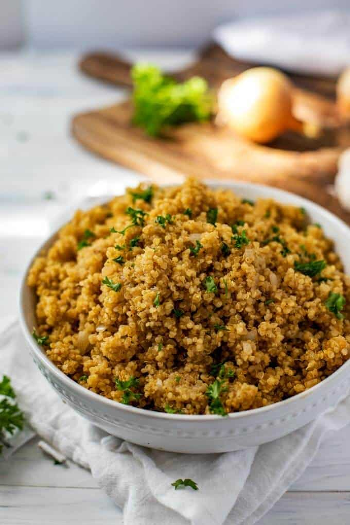 Photo of a big white bowl filled with Instant Pot Quinoa garnished with parsley.
