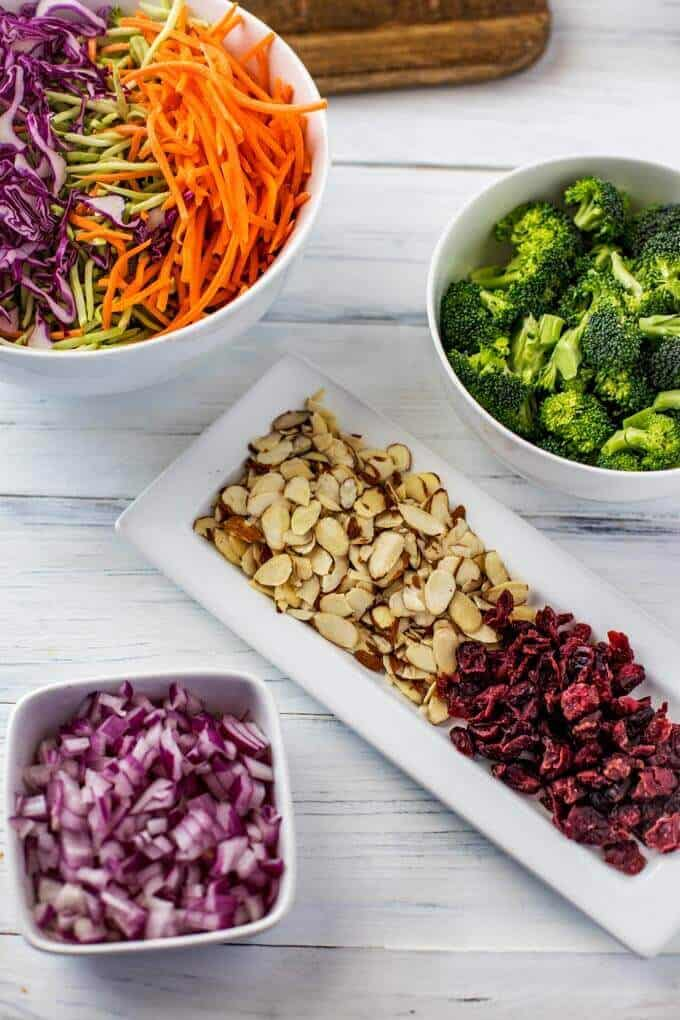 Photo of ingredients for a Broccoli Slaw Salad Recipe in small white dishes - broccoli slaw, cabbage, shredded carrots, broccoli, red onion, almonds and cranberries.