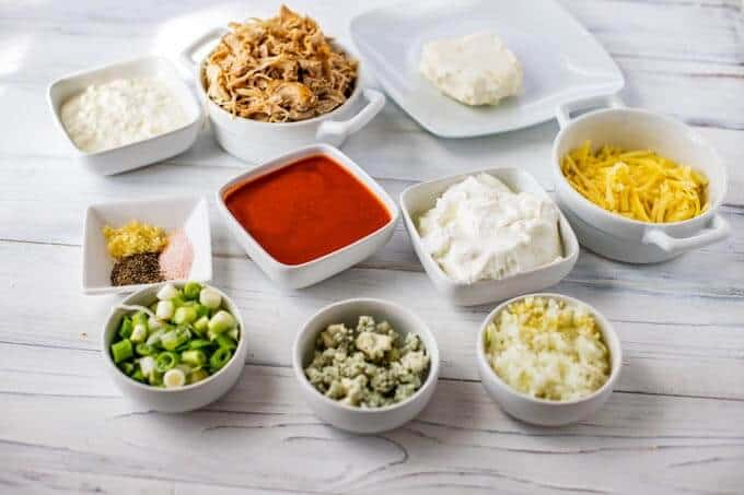 Photo of the ingredients for a Healthy Buffalo Chicken Dip with Greek Yogurt, cottage cheese, low fat cream cheese, chicken, cheese, seasonings, scallions, blue cheese onion and garlic.