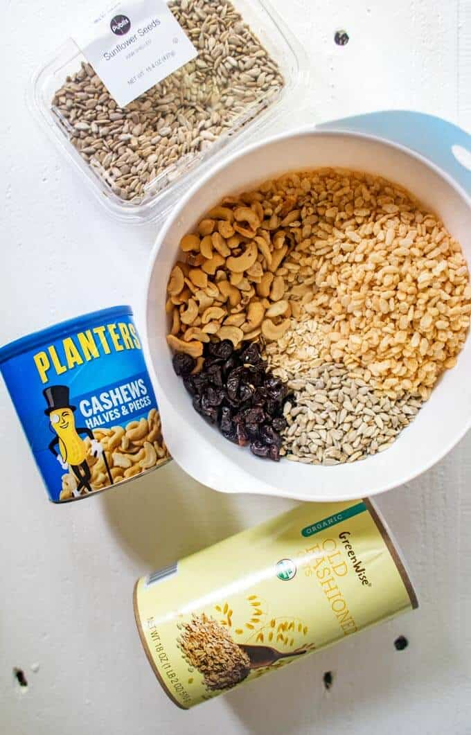 Photo of dry ingredients for a homemade granola bar recipe mixed together in a bowl with the ingredient packaging surrounding.