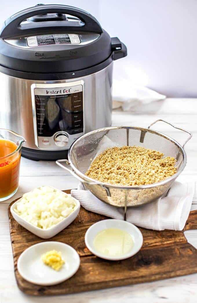 Photo of an Instant Pot with a cutting board in front of it that has quinoa in a strainer, onion, and garlic sitting on it in prep bowls with a measuring cup with broth next to it.