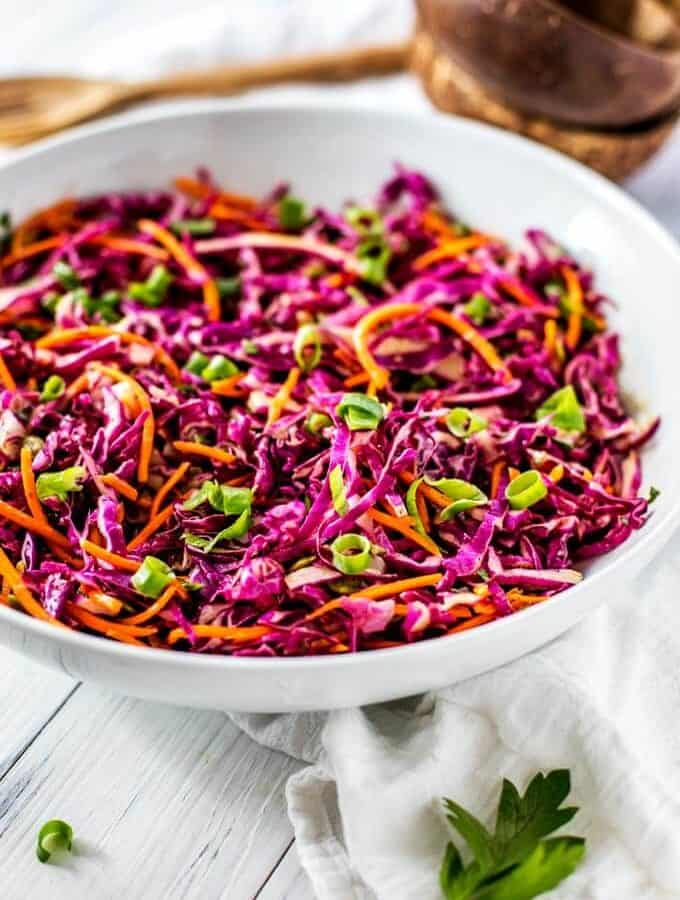 Photo of No Mayo Coleslaw in a white serving dish garnished with scallions.