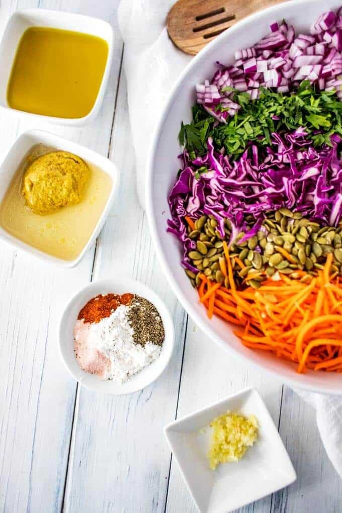Photo of Shredded red cabbage, carrots, red onion, chopped parsley, pepitas, olive oil, rice wine vinegar, spicy mustard, Swerve, miced garlic, cayenne pepper, salt, and pepper in white prep bowls.