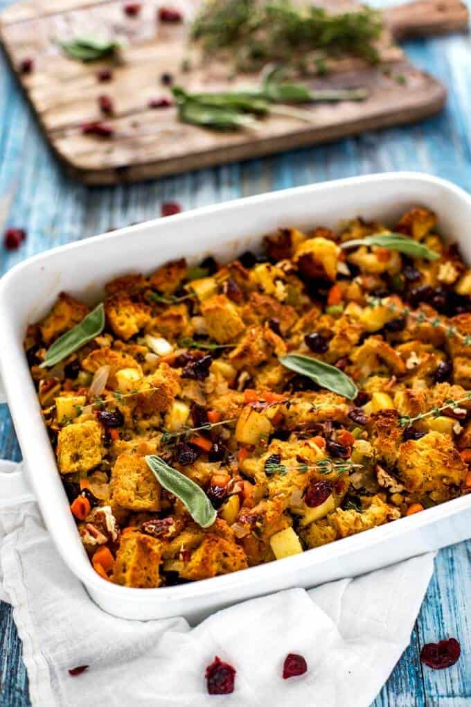 Photo of Gluten Free Stuffing in a white casserole dish garnished with sage and thyme.