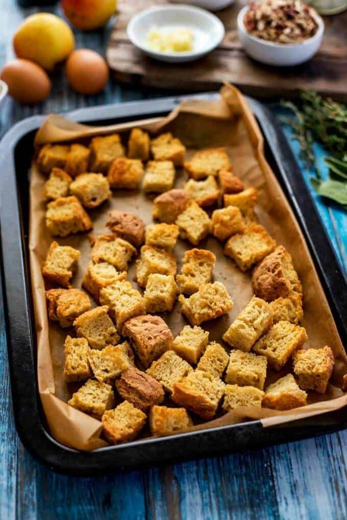 Photo of a baking sheet with toasted bread cubes on it.
