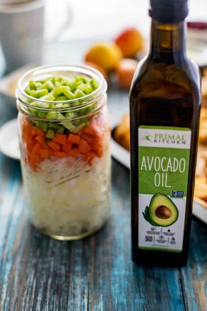 Photo of a mason jar with chopped onion, carrot, and celery and a bottle of avocado oil.