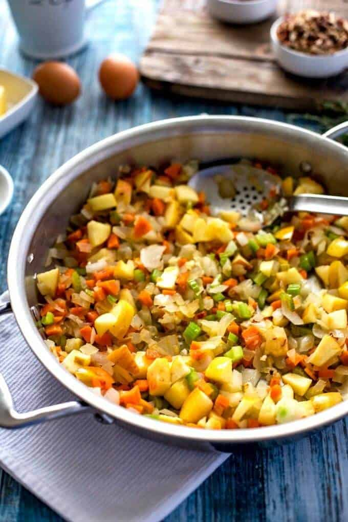 Skillet with onion, carrot, celery, and apple cooking.