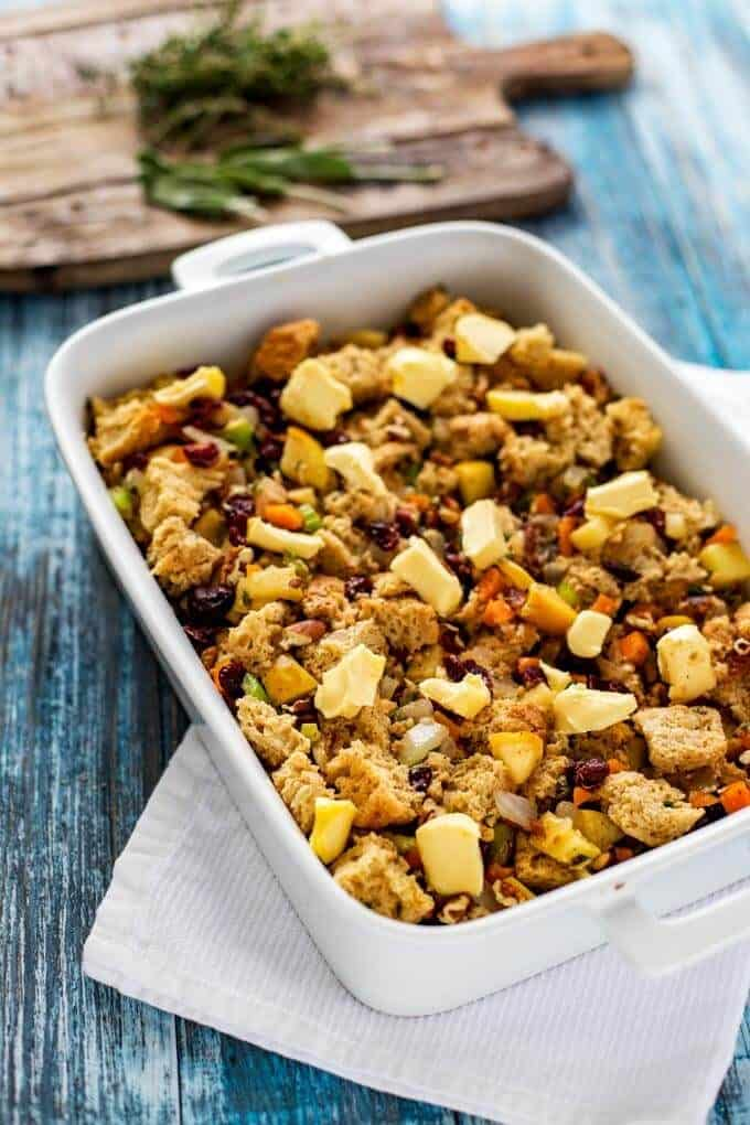 Photo of gluten free stuffing in a white casserole dish with butter dotted over it.