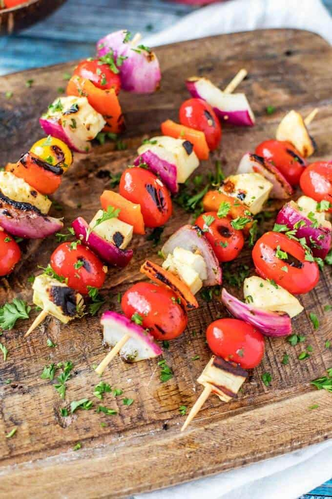 Photo of four Halloumi Kebabs on a dark wood cutting board garnished with parsley.