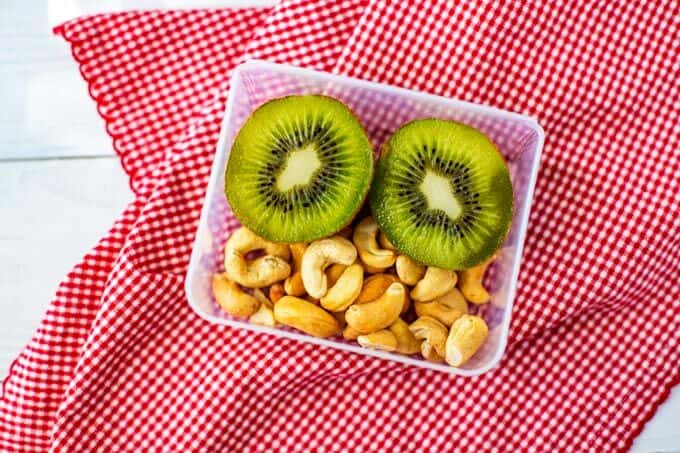 Photo of a kiwi cut in half and cashews in a small plastic lunch box container.