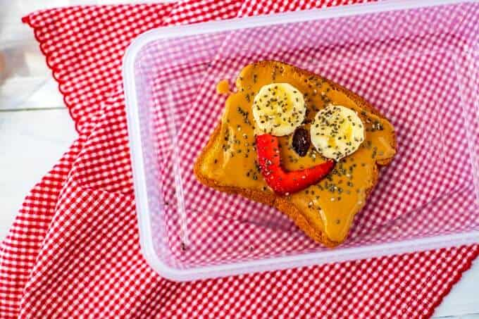 Photo of toast with nut butter and a smiley face made of two banana slices for eyes, strawberry lips and a raisin all sprinkled with chia seeds.