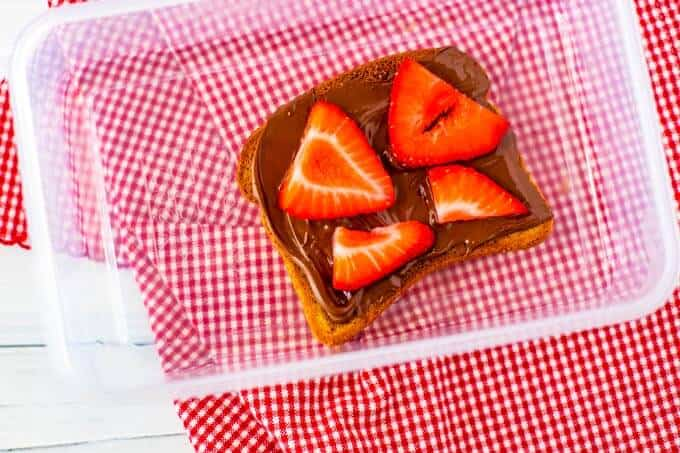 Photo of Chocolate Hazelnut Butter toast topped with strawberries in a plastic container.