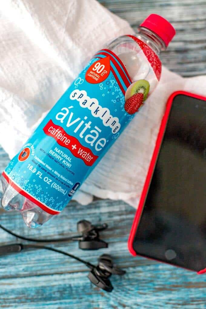 Photo of a bottle of Avitae sparkling water, an iPhone, and headphone for ways to boost your energy.