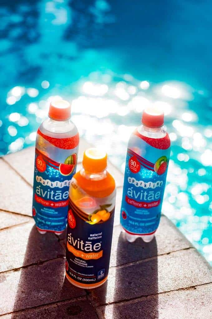 Three bottles of caffeinated water next to a pool for ways to boost your energy.