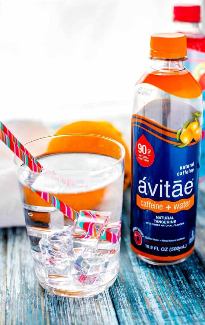 Photo of a glass of caffeinated water with ice and a straw and a bottle of avitae next to it.