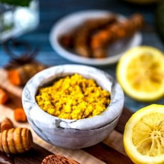 Photo of a DIY Turmeric Face Mask in a small marble bowl surrounded by lemon, honey, and fresh turmeric.