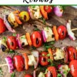 """Photo of Halloumi Kebabs on a wooden cutting board with the text """"Halloumi Kebabs"""" above it."""