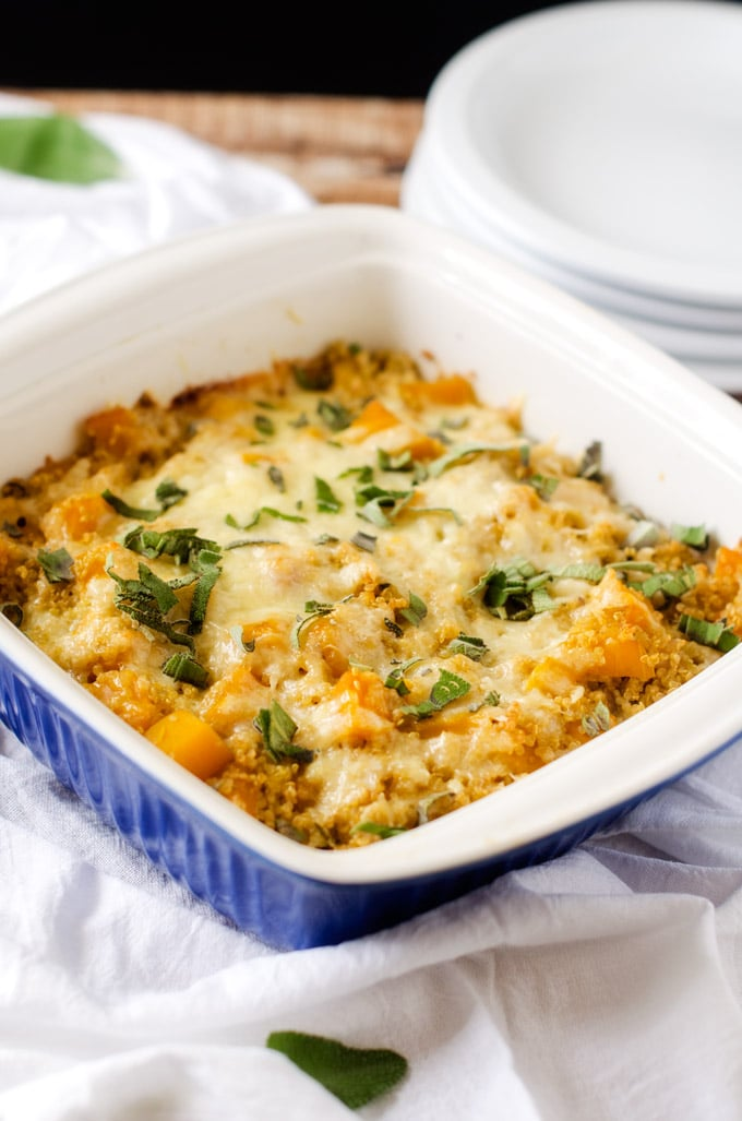 Photo of Butternut Squash Casserole with Quinoa in a blue casserole dish with serving plates behind it.